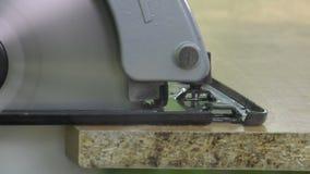Cutting a panel with a circular saw. Electric saw progress during cutting operation, closeup stock footage