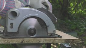 Cutting a panel with a circular saw. Electric saw progress during cutting operation, closeup stock video