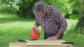 Cutting a panel with a jigsaw. Man cutting a heart in a panel of wood particles stock video footage