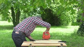 Cutting a panel with a jigsaw. Man cutting a heart in a panel of wood particles stock footage