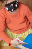 Cutting the paper. Girl with black and white paint on her face cut the paper with scissors Stock Image