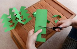 Cutting a paper Christmas tree chain Stock Images