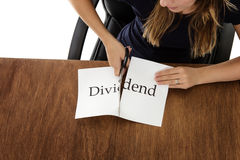 Cutting paper. Woman shot from above cutting paper in half with the word dividend written on Stock Image