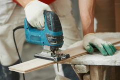 Cutting parquet board with jigsaw Royalty Free Stock Photo