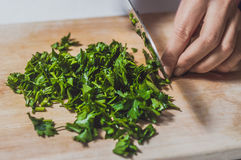 Cutting parsely on wood Royalty Free Stock Photo