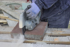Cutting Pavings Stones. With a grinder at construction site Royalty Free Stock Photo
