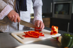 Cutting pepper. Preparing red pepper in kitchen Stock Images