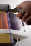 Cutting Photos. A paper cutter being used to cut two glossy photos stock image