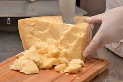 Cutting a piece of Parmesan Royalty Free Stock Photos