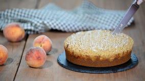 Cutting a piece of peach crumble cake.