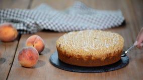 Cutting a piece of peach crumble cake