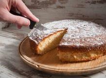 Cutting a piece of sponge cake Stock Image