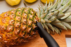 Cutting pineapple. On a wooden board Royalty Free Stock Photography