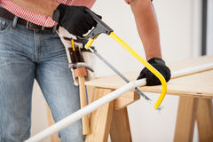 Cutting pipes with a hacksaw. Closeup of a plumber using a hacksaw to cut down some pipes stock photography