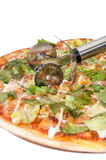 Cutting pizza with letuce with metal pizza cutter.  Stock Images