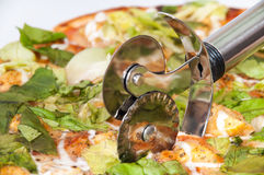 Cutting pizza with letuce with metal pizza cutter.  Stock Photography