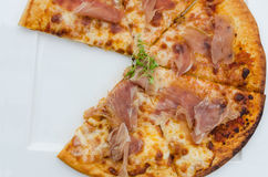 Cutting pizza in pieces. On white plate Royalty Free Stock Images