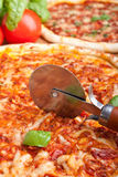 Cutting pizza with a pizza-knife Stock Images