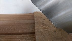 Cutting plank with hand saw Stock Images