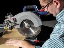 Cutting plank with mitre saw stock images