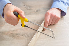 Cutting plastic molding with handsaw Royalty Free Stock Photo