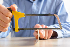 Cutting plastic molding with handsaw Royalty Free Stock Photos