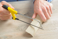 Cutting plastic molding with handsaw Royalty Free Stock Photography