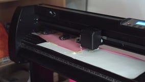 Cutting plotter. Plotter cuts vinyl, film. Laser cuts vinyl, film. Industrial equipment for cutting vinyl and film. Cutting plotter. Plotter cuts pink vinyl stock video