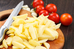 Cutting potatoes on a board Royalty Free Stock Photography