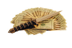 Cutting prices. Money in the form of many large bills with a dagger representing cutting prices Stock Images