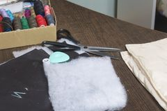 Cutting of the product for sewing. On the table is a cloth with chalk-marked garments. Nearby lie scissors, chalk and a box with c Royalty Free Stock Images