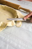 Cutting raw dough at the edges of the mold Royalty Free Stock Photos