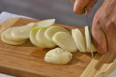 Cutting raw onions on a wooden board Royalty Free Stock Images