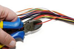 Cutting red cable with nippers royalty free stock photo