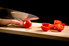 Cutting red cherry tomatoes on wooden board Stock Photo