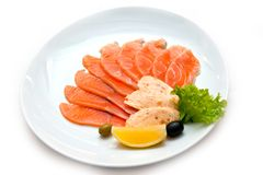 Cutting red fish with an orange slice in greens and olives stock images