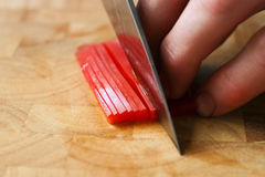 Cutting red peppers Royalty Free Stock Image