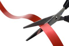Cutting Red Ribbon. Closeup image of scissors cutting a red ribbon royalty free stock photo