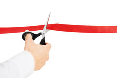 Cutting Red Ribbon. Person cutting red ribbon with scissors on white background Stock Images