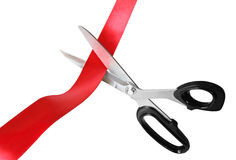 Cutting Red Tape. Scissors cutting through red ribbon or tape, isolated on white Stock Images