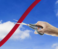 Cutting red tape. Male hand cutting red tape on sky background Royalty Free Stock Photography