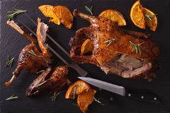 Cutting the roast duck and oranges on a slate board. Horizontal Stock Images