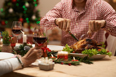 Cutting roasted chicken. Cropped image of men cutting roasted chicken at the Christmas family dinner Stock Photo