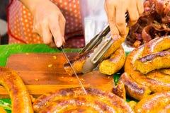 Cutting Sai Aua (Notrhern Thai Spicy Sausage ). In the market Royalty Free Stock Photos