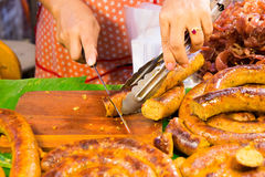Cutting Sai Aua (Notrhern Thai Spicy Sausage ). In the market Royalty Free Stock Photography