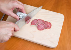Cutting salami on board. Cutting salami on a wooden board Royalty Free Stock Images