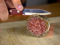 Cutting salami on a wooden board Royalty Free Stock Photography