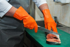 Cutting salmon fish. Chef cutting salmon fish on steaks with knife Stock Photography