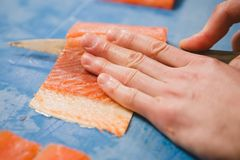 Cutting the salmon with a knife Stock Photos