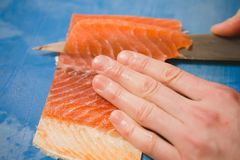 Cutting the salmon with a knife Royalty Free Stock Images